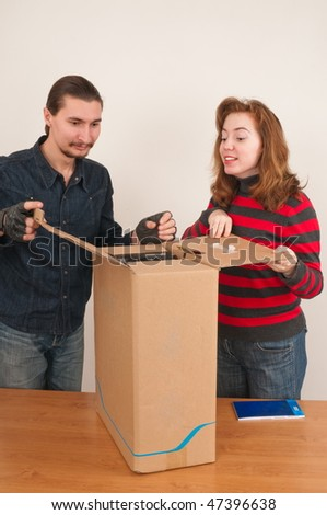 Married couple and in a cardboard box the computer. - stock photo