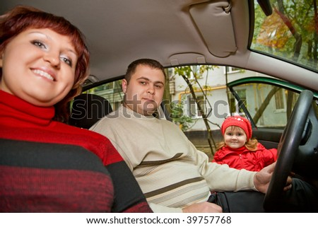 Married couple and  little girl sit in car near a building - stock photo