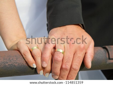 married couple holds hands and shows of there golden wedding rings - stock photo