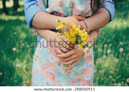 Married couple in love, man embraces a woman in summer park. Woman holding bouquet of yellow dandelions. Focus on flowers - stock photo