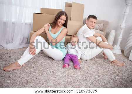 Married couple is moving in another house. They are sitting on floor with their small daughter and smiling. There are boxes behind them - stock photo