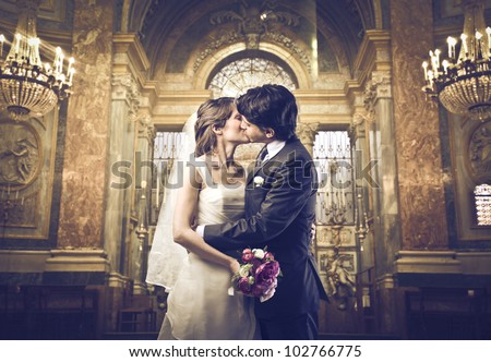 Married couple kissing in a church - stock photo