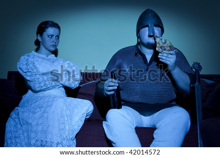 Married couple of medieval times by the TV - stock photo