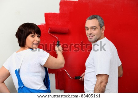 Married couple painting wall - stock photo