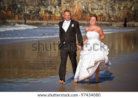 Married couple run on the beach