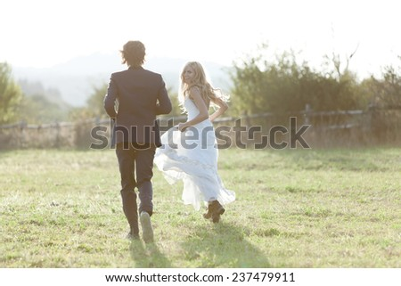 Married couple running in a field, having fun and smiling. She is looking back. - stock photo
