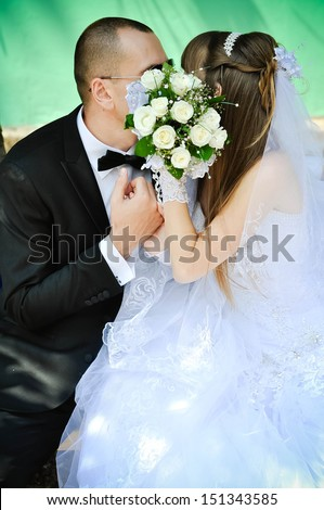 Married couple sharing a kiss behind the bouquet
