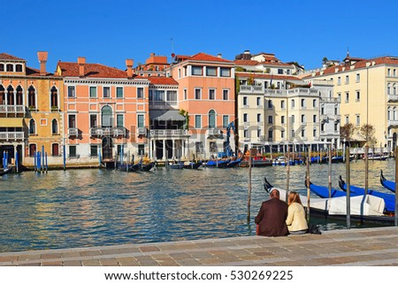 married couple sits on the waterfront of Grand Canal in Venice, Italy