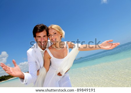 Married couple standing by blue lagoon - stock photo