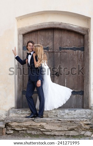 Married couple standing in front of an old wooden gate, on some old stairs. She gives him a sweet embrace and he reply with a slick glare. - stock photo