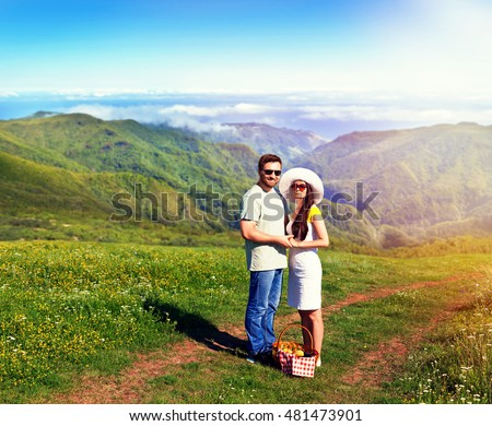 Married couple with picnic basket standing in the park