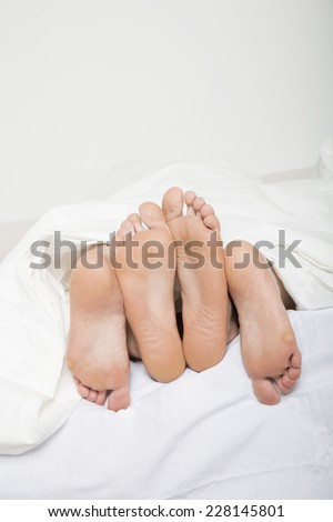 Married couples feet in bed