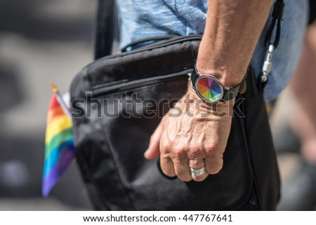 Married man in the crowd celebrating Pride Parade. Wearing colorful rainbow watch and a flag. During a march supporting marriage equality and LGBT rights.  - stock photo