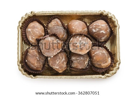 marron glace on golden tray on white background