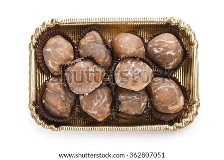 marron glace on golden tray on white background - stock photo