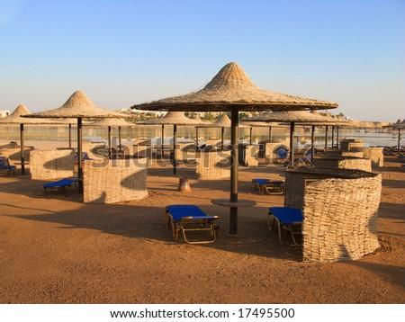 Marsa Alam beach with umbrellas and a blue sky - stock photo