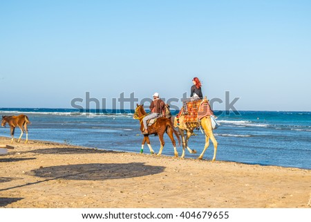 MARSA ALAM, EGYPT, MARCH 31, 2016: Female tourist  rides on camel on seashore of Red Sea accompanied by local guide on horse