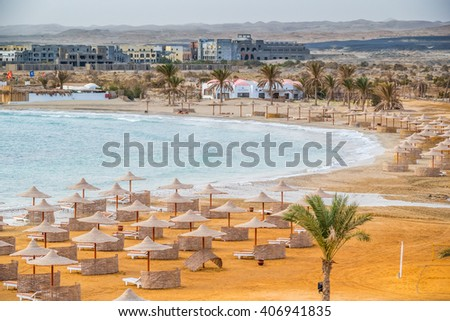 MARSA ALAM, EGYPT, MARCH 28, 2016:  Three Corners Equinox Beach Hotel at Red Sea shore - long beach with umbrellas - stock photo