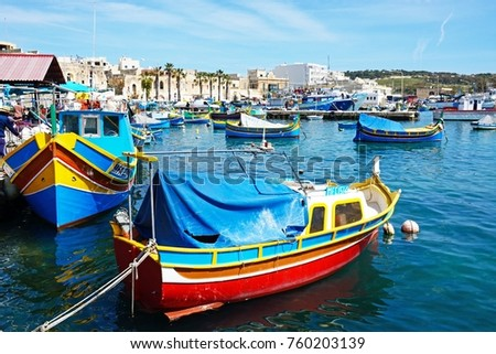 MARSAXLOKK, MALTA - APRIL 1, 2017 - Traditional Maltese Dghajsa fishing boats in the harbour with waterfront buildings to the rear, Marsaxlokk, Malta, Europe, April 1, 2017.