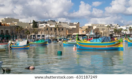 MARSAXLOKK, MALTA - 24 JANUARY 2017: Colourful, traditional Luzza boats in the harbour of the fishing village of Marsaxlokk