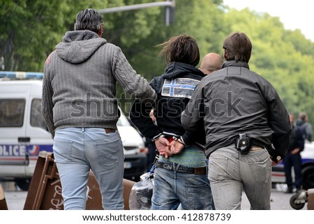 Marseille, France - April 28, 2016 : Student arrested and handcuffed by two plainclothes officers during clashes between protesters and french riot police during a demonstration against the labor law - stock photo