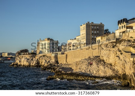 MARSEILLE, FRANCE - JULY 9, 2015 : people enjoy sunset at the Corniche Kennedy in Marseille, France. The Corniche is a famous tourist spot and old historic hotels offer accomodation. - stock photo