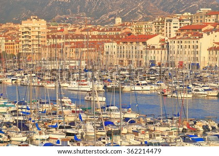 Marseille harbor with yacht and leisure boats surrounded by historical buildings at sunset, France - stock photo