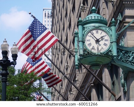 Marshall Field's clock over american flags on State Street in Chicago, USA - stock photo