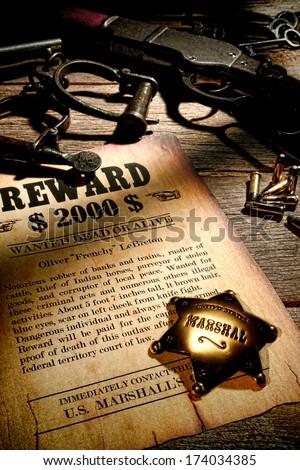 Marshall lawman antique brass star badge on old wanted reward fugitive poster with western prison shackles and vintage rifle gun with bullets on law enforcement officer wood desk in sheriff office  - stock photo