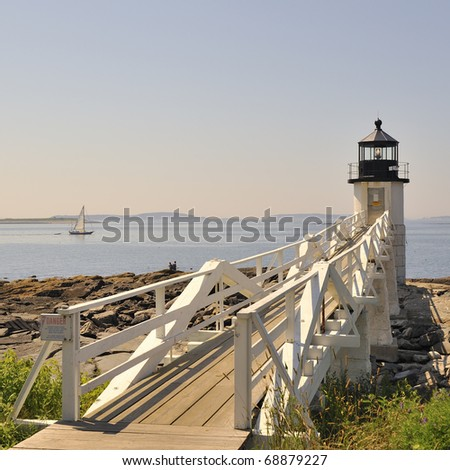 Marshall Point Lighthouse and sailboat sailing on the water in Penobscot Bay with copy space Port Clyde St. George Peninsula, Maine. A beautiful New England summer day with a white wooden light house - stock photo
