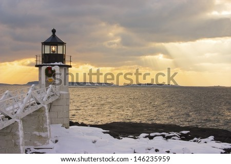 Marshall Point Lighthouse with breaking clouds after snowstorm. - stock photo