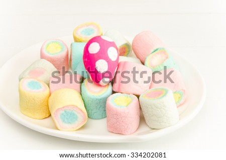 Marshmallow and Easter egg in white plate and white table, background - stock photo