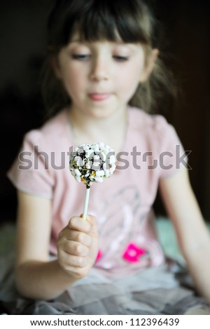 Marshmallow cake on a stick in the hand of a little girl, focus on a marshmallow - stock photo