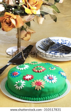 Marshmallow foundant cake decorated with flowers next to saucers silver sweet forks and cake slice - stock photo