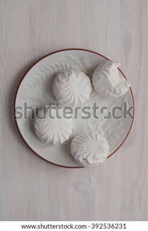 Marshmallow or vanilla zephyr on white dish on a light wooden background. View from top. One piece of marshmallow is bitten. Zephyr - export commodity of Latvia. - stock photo