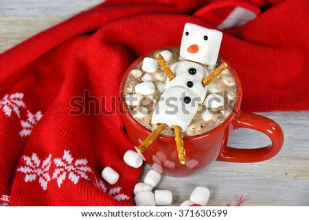 marshmallow snowman in hot chocolate drink with red scarf on wood - stock photo