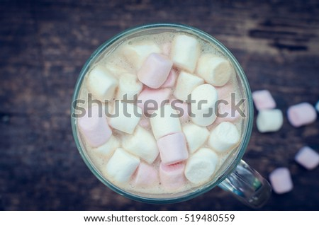 Marshmallows on the top of a hot chocolate drink in a glass on wooden background. Fluffy, hot chocolate, cappuccino, coffee in a cup with marshmallow. Christmas drink. Top view.