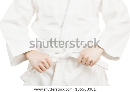 Martial art fighter holding his belt on a white background - stock photo