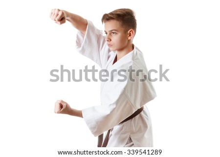 Martial art sport karate - child teen boy in white kimono training karate punch and block