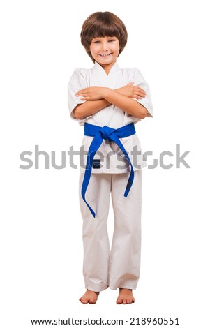 Martial arts boy. Full length of little boy training karate while isolated on white background - stock photo