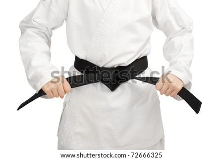 Martial arts boy tying the knot to his black belt - stock photo