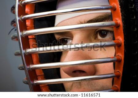 Martial arts concept portrait Man in kendo helmet closeup on eyes - stock photo