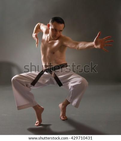 Martial arts fighter acting. Artistic studio lighting.  - stock photo