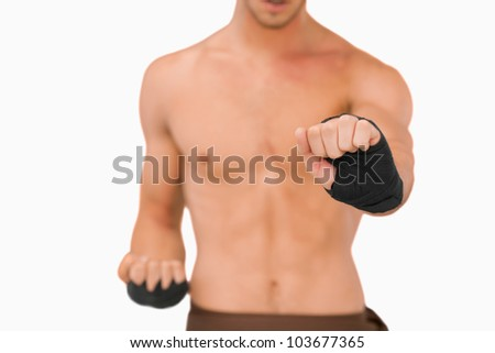 Martial arts fighter doing his exercises against a white background - stock photo