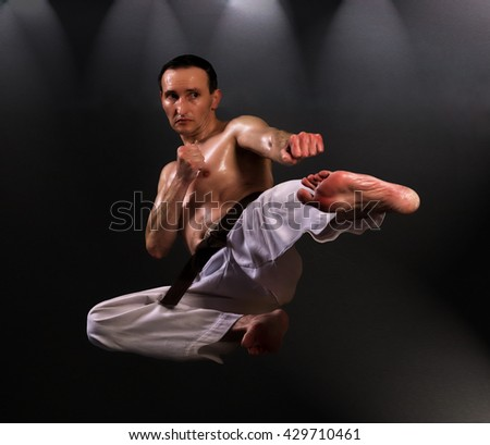 Martial arts fighter kicking. Artistic studio lighting.   - stock photo