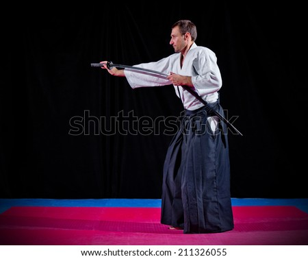 Martial arts fighter with katana on black - stock photo