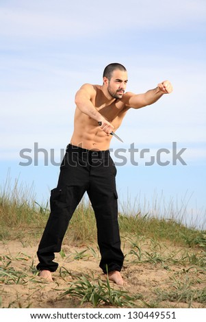 martial arts instructor holding a knife and practicing outdoor - stock photo