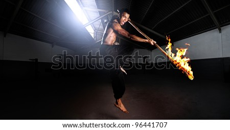 Martial arts kung fu master strikes with a burning stick in self defense. set in a training gym dojo, traditional dangerous sport fitness training. Large file, HDR composite panorama - stock photo