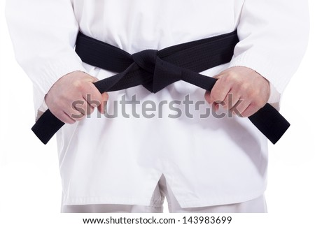 Martial arts man tying his black belt, isolated on white - stock photo