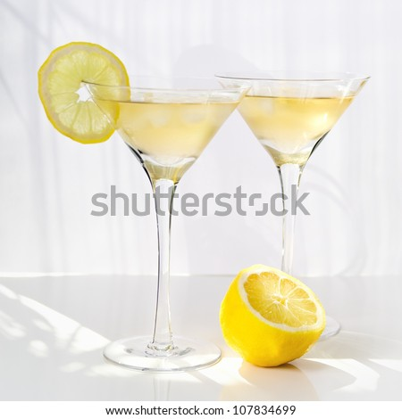 Martini alcohol cocktail with yellow lemon on white - stock photo